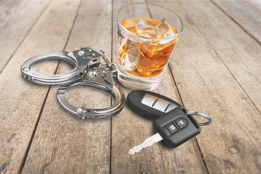 glass of liquor car keys and handcuffs